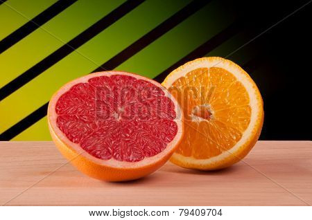 Half of grapefruit and orange on a wooden surface with a gradient abstract background