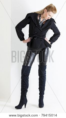 standing woman wearing black clothes and black boots