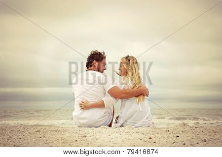Happy Couple Sitting On Beach Looking At Each Other