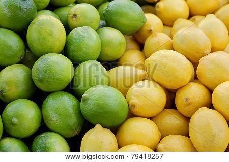 Pile Of Fresh Yellow Lemons And Green Limes At Farmer's Market