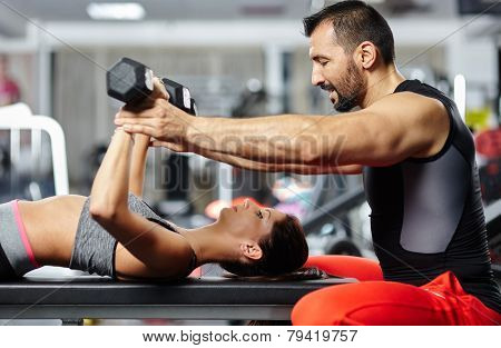 Fitness Instructor Assisting Young Woman
