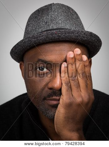 Black Man In Hat With Stubble Covering One Eye