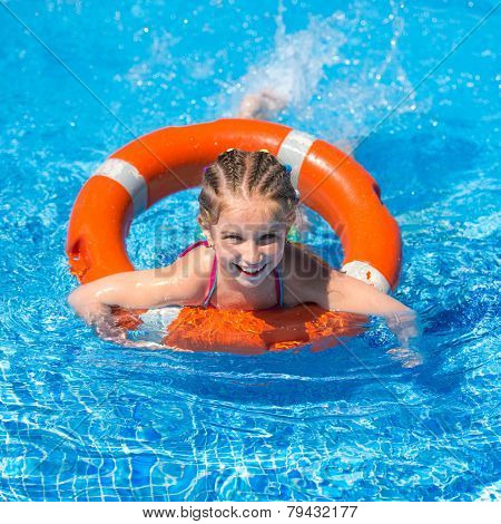 smiling little girl swims with a lifeline in the pool in  summer