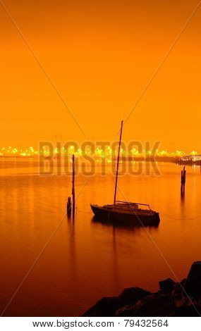 Boat anchored on calm water at night