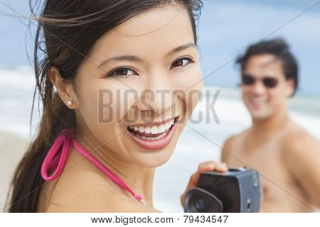 Man & woman Asian couple, boyfriend girlfriend in bikini, taking vacation video or photograph at the beach
