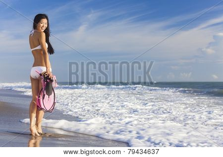 Rear view of beautiful young Asian Chinese woman in bikini with snorkel, mask & flippers on a deserted beach with blue sky