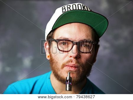 Young man with vapor cigarette stem