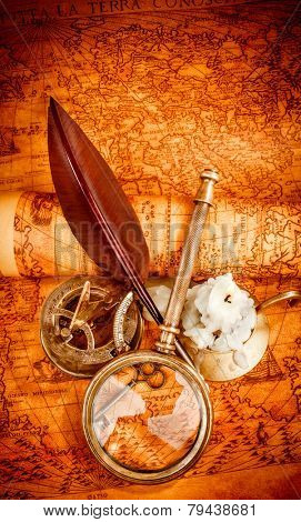 Vintage compass, magnifying glass, pocket watch, quill pen, spyglass lie on an old ancient map in 1565 with a lit candle. Vintage still life.