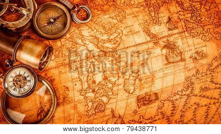 Vintage magnifying glass, compass, telescope and a pocket watch lying on an old map in 1565.