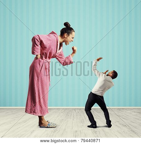 displeased woman screaming and looking at small scared man