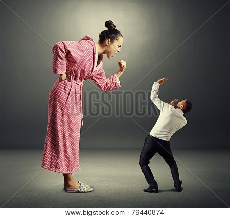 angry woman in pink dressing gown screaming at small startled man in the dark room
