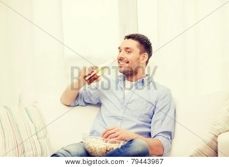 home, technology and entretainment concept - smiling man with beer and popcorn at home