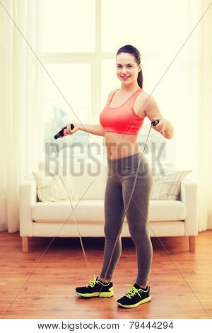 fitness, home and diet concept - smiling teenage girl with skipping rope at home