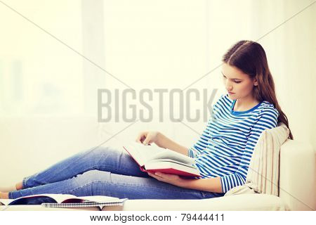 leasure and home concept - calm teenage girl woman reading book and sitting on couch at home