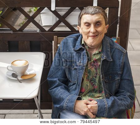 Disabled man with cerebral palsy sitting at outdoor cafe with a cappuccino.