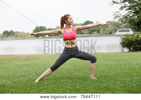 Yoga Virabhadrasana Ii Warrior Pose By Woman On Lawn,right Side