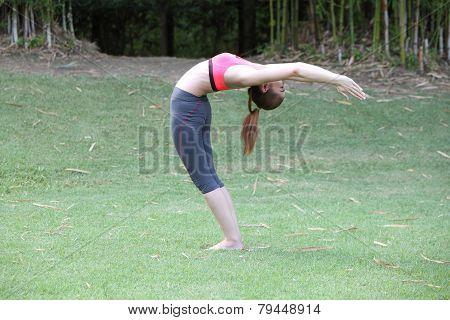 Yoga Ardha Chandrasana (back Bend) Pose By Woman On Lawn