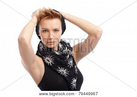 Pretty gingerish woman in cap and scarf wearing sleeveless top, hands behind head.