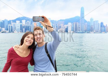 Selfie tourists couple taking self-portrait picture photos in Hong Kong enjoying sightseeing on Tsim Sha Tsui Promenade and Avenue of Stars in Victoria Harbour, Kowloon, Hong Kong. Travel concept.