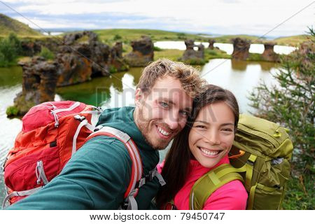 Selfie - travel couple on lake Myvatn Iceland. Friends taking selfies photo having fun traveling together visiting Icelandic tourist destination landmarks. Lake Myvatn lava columns, Iceland.