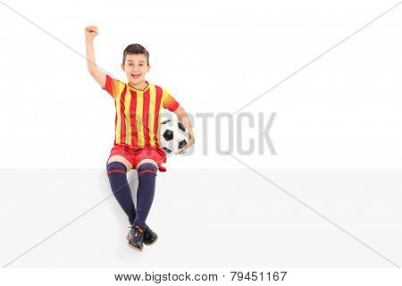 Junior soccer player gesturing joy seated on a panel isolated on white background
