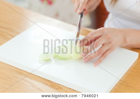 Delighted Woman Preparing Oinion In The Kitchen