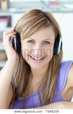 Delighted Woman Using Headphone In The Kitchen