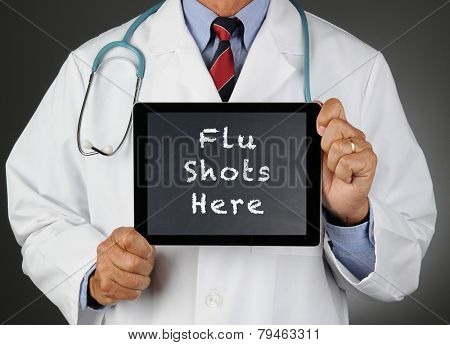 Closeup of a doctor holding a tablet computer with a chalkboard screen with the words Flu Shots Here. Man is unrecognizable.