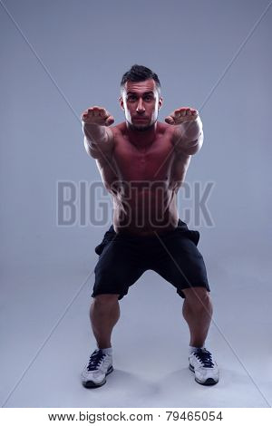 Muscular handsome man doing squats over gray background