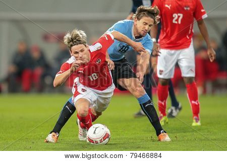 KLAGENFURT, AUSTRIA - MARCH 05, 2014: Christoph Leitgeb (#18 Austria) and Gaston Ramirez (#18 Uruguay) fight for the ball in a friendly soccer game between Austria and Uruguay.