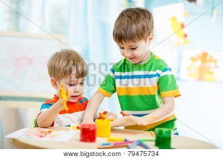 smiling kids play and paint at home or kindergarten or playschool or daycare