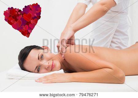 Beautiful brunette enjoying a back massage smiling at camera against heart