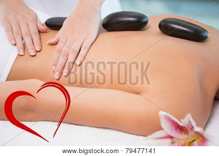 Beautiful woman receiving stone massage at health farm against heart