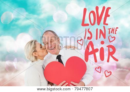 Older affectionate couple holding red heart shape against digitally generated pink and blue girly design