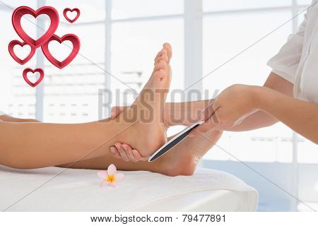 Side view of a young woman receiving pedicure treatment against pink hearts