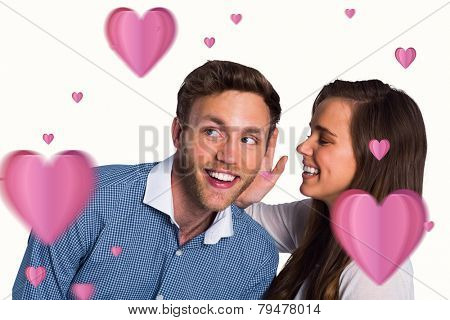 Happy young woman whispering secret into friends ear against hearts