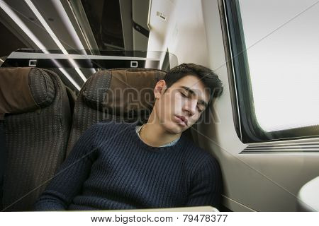 Young man sleeping while traveling on a train sitting in passenger coach