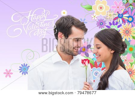 Handsome man offering his girlfriend a rose against digitally generated girly floral design