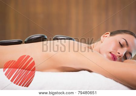 Beautiful woman receiving stone massage at health farm against red heart