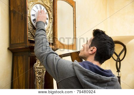 Young man checking a pendulum and winding the mechanism