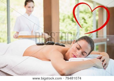 Beautiful woman receiving stone massage at health farm against heart