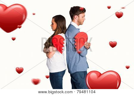 Side view of young couple holding broken heart against hearts