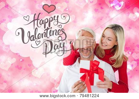 Loving couple with gift against digitally generated girly heart design