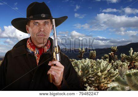 Cowboy With Gun Touching Hat In Cholla Garden