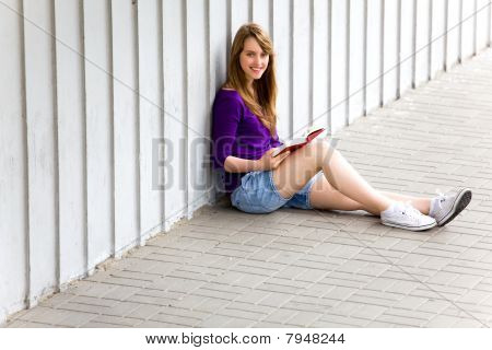 Teenage girl sitting with book
