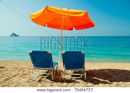Blue Sunbeds And Orange Umbrella (parasol) On Paradise Beach In Corfu Island, Greece.