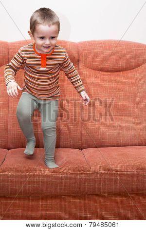 Happy Child Jumping On Sofa