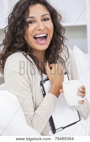 Beautiful young Latina Hispanic woman smiling, laughing, relaxing and drinking a cup of coffee or tea using tablet computer