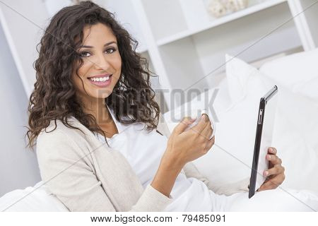 Beautiful young Latina Hispanic woman smiling, relaxing and drinking a cup of coffee or tea using tablet computer