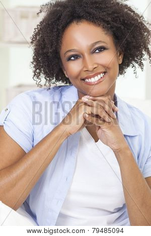 A beautiful black mixed race African American girl or young woman looking happy and smiling